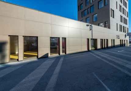 Dieses Büro- und Geschäftshaus besticht mit seiner gedunkeltem Messing und Goldbronze changierenden Haut.